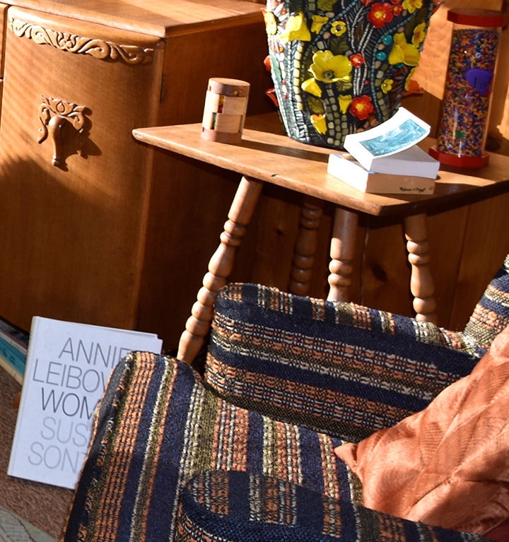 easy chair, wooden end table, and lamp with a floral pattern base