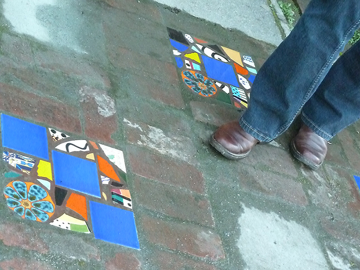 Janet's feet in brown leather shoes with tile mosaics on the ground